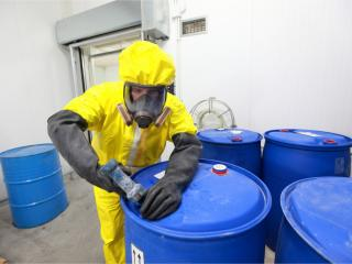 man in protective suit with chemical waste drums